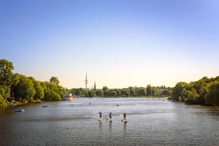 Alster Lake in Hamburg with people paddleboarding and the TV tower in the background Imagens