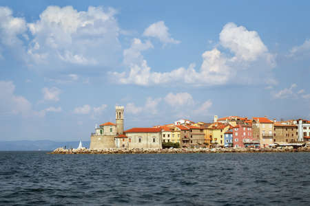 Lighthouse and church in Piran, Slovenia, view from the sea Imagens