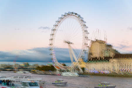 London, United Kingdom - October 26th 2018: Double exposure of the London Eye  on the South Bank of the River Thames, in dusk