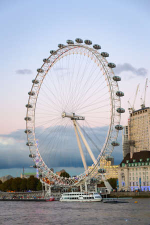 London, United Kingdom - October 26th 2018: London Eye  with tourtic boat on the River Thames,  in dusk