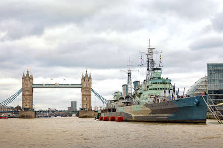 Tower Bridge and HMS Belfast with tourists in autumn