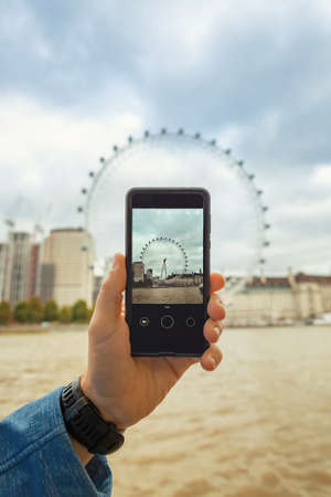 London, United Kingdom - October 26th 2018: Tourist with the cellphone, taking photo of the London Eye, ferris wheel