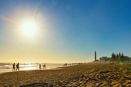 Lighthouse in Maspalomas, with tourists walking on the beach, Gran Canaria, Canary islands Imagens