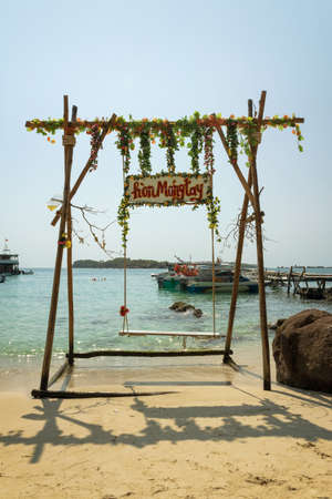 Swing on the beach on the Fingernail Island with the wooden board showing the name of the island written in vietnamese (Hon Mong Tay), Vietnam