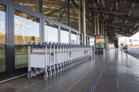 Hamburg, Germany - March 29 2020: Stacked airport trolleys in front of the departure terminal at airport in Hamburg, not in use because of the covid-19 pandemic
