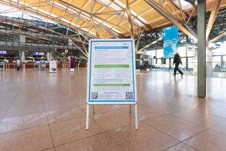Hamburg, Germany - March 29 2020: Notice about the Coronavirus from the german Federal Ministry of Health, with the basic info about the virus on German, hotlines and web links, at the empty airport Banque d'images - 143991990