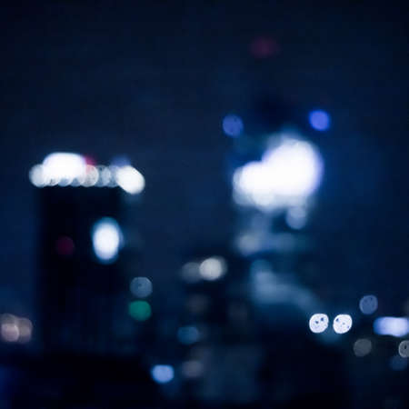 Blurry metropolitan district - night life, abstract background and modern dark tones concept. Big city comes alive at night Imagens