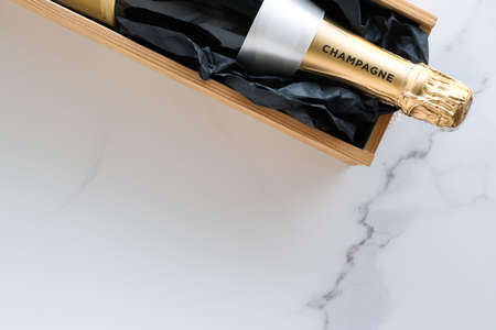 Wedding celebration, lifestyle and luxury present concept - A champagne bottle and a gift box on marble