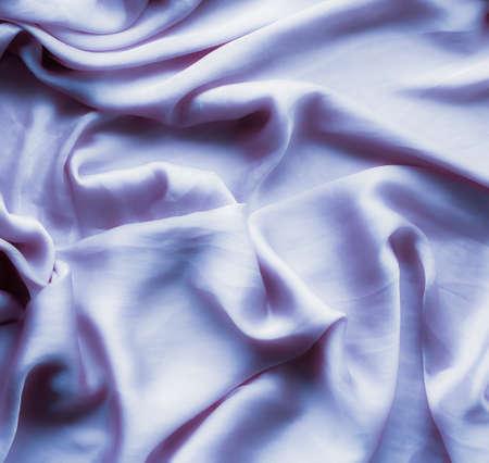 Textura de tela elegante, telón de fondo abstracto y concepto moderno de colores pastel: ondas de seda suave púrpura, fondo flatlay