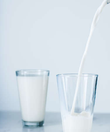 Dairy, healthy nutrition and breakfast concept - World Milk Day, pouring into glass on marble table