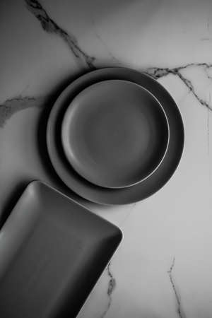 Black empty plate on marble, flatlay - stylish tableware, table decor and food menu concept. Serve the perfect dish
