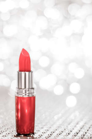 Cosmetic branding, sale and glamour concept - Coral lipstick on silver Christmas, New Years and Valentines Day holiday glitter background, make-up and cosmetics product for luxury beauty brand
