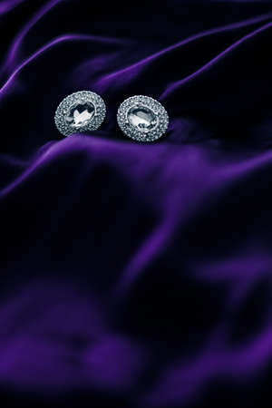 Jewellery brand, elegant fashion and bridal luxe gift concept - Luxury diamond earrings on dark violet silk fabric, holiday glamour jewelery present Stock Photo