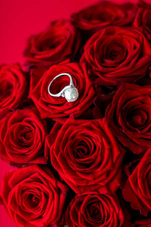 Gemstone jewellery, wedding present and engagement proposal concept - Beautiful white gold pearl ring and bouquet of red roses, luxury jewelry love gift on Valentines Day and romantic holidays Stock Photo