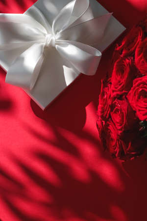 Happy holidays, luxe shopping and love gifts concept - Luxury holiday silk gift box and bouquet of roses on red background, romantic surprise and flowers as birthday or Valentines Day present Stock Photo - 132095560