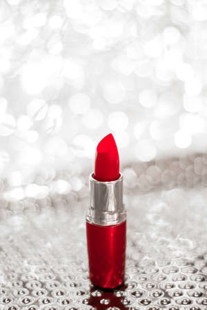 Cosmetic branding, sale and glamour concept - Red lipstick on silver Christmas, New Years and Valentines Day holiday glitter background, make-up and cosmetics product for luxury beauty brand