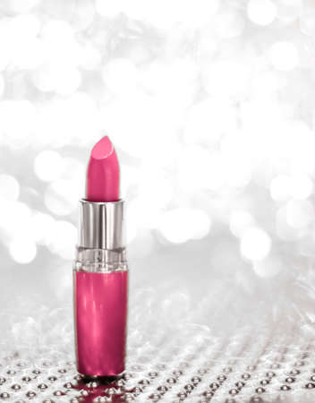 Cosmetic branding, sale and glamour concept - Pink lipstick on silver Christmas, New Years and Valentines Day holiday glitter background, make-up and cosmetics product for luxury beauty brand