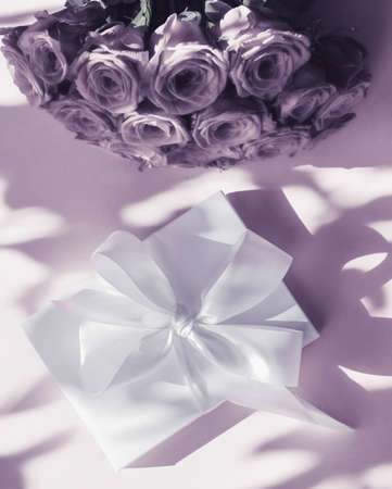Happy holidays, luxe shopping and love gifts concept - Luxury holiday silk gift box and bouquet of roses on purple background, romantic surprise and flowers as birthday or Valentines Day present