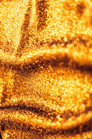 Luxe glowing texture, night club branding and New Years party concept - Golden holiday sparkling glitter abstract background, luxury shiny fabric material for glamour design and festive invitation