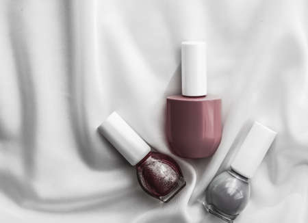 Cosmetic branding, salon and glamour concept - Nail polish bottles on silk background, french manicure products and nailpolish make-up cosmetics for luxury beauty brand and holiday flatlay art design