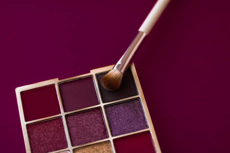 Cosmetic branding, mua and girly concept - Eyeshadow palette and make-up brush on wine background, eye shadows cosmetics product for luxury beauty brand promotion and holiday fashion blog design