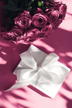 Happy holidays, luxe shopping and love gifts concept - Luxury holiday silk gift box and bouquet of roses on pink background, romantic surprise and flowers as birthday or Valentines Day present