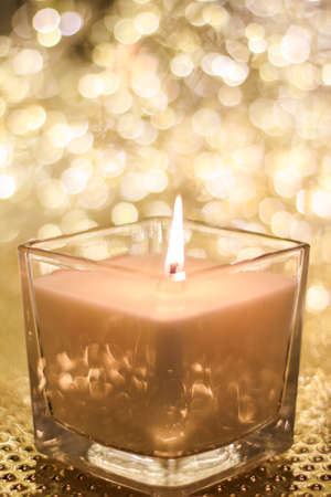 Festive decoration, branding and aromatherapy spa concept - Aromatic candle on golden Christmas and New Years glitter background, Valentines Day luxury home decor and holiday season brand design Stock Photo