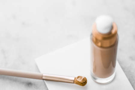 Cosmetic branding, glamour and skincare concept - Makeup foundation bottle and contouring brush on marble, make-up concealer bb cream as cosmetics product for luxury beauty brand holiday design