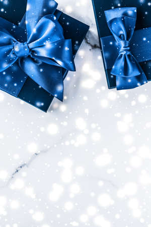 Branding, glamour and cold season concept - Winter holiday gift box with blue silk bow, snow glitter on marble background as Christmas and New Years presents for luxury beauty brand, flatlay design Stock Photo