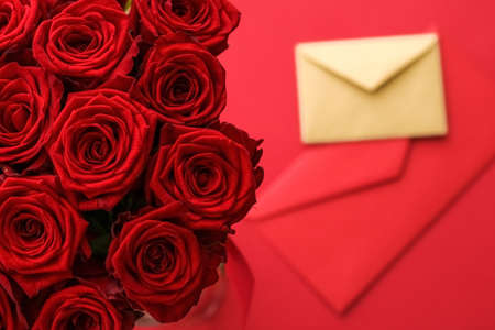 Holiday gift, flowers flatlay and happy relationship concept - Love letter and flower delivery service on Valentines Day, luxury bouquet of red roses and card envelopes on red background