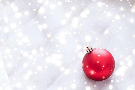 Decoración de regalo, Nochevieja y concepto de celebración feliz: adornos navideños rojos sobre piel esponjosa con brillo de nieve, fondo de diseño de vacaciones de invierno de lujo