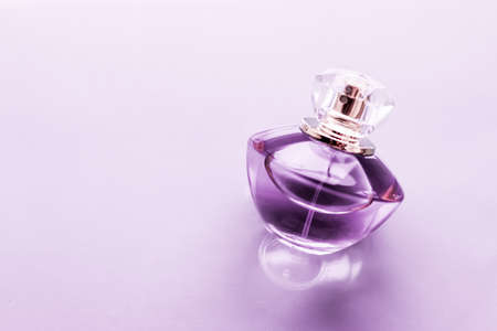 Perfumery, spa and branding concept - Purple perfume bottle on glossy background, sweet floral scent, glamour fragrance and eau de parfum as holiday gift and luxury beauty cosmetics brand design Stock Photo