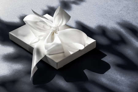 Anniversary celebration, shop sale promotion and luxe surprise concept - Luxury holiday white gift box with silk ribbon and bow on black background, luxe wedding or birthday present