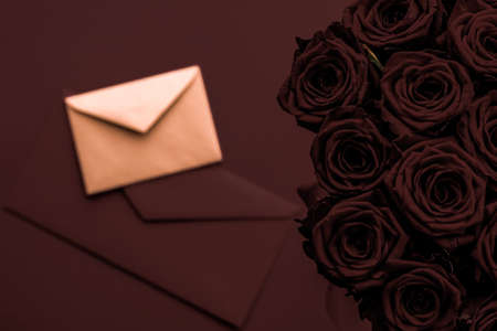 Holidays gift, floral present and happy relationship concept - Love letter and flowers delivery on Valentines Day, luxury bouquet of roses and card on chocolate background for romantic holiday design