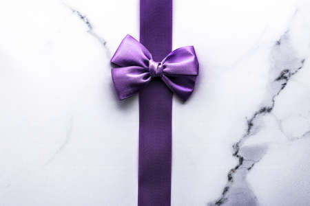 Happy holidays, festive decoration and brand sale promotion concept - Purple silk ribbon and bow on luxury marble background, holiday flatlay backdrop