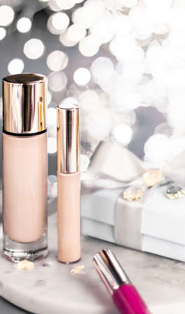 Cosmetic branding, Christmas glitter and girly blog concept - Holiday make-up foundation base, concealer and white gift box, luxury cosmetics present and blank label products for beauty brand design Stock Photo