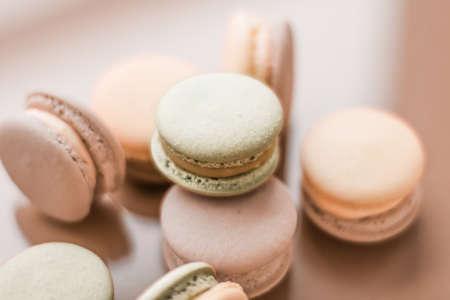 Concept de pâtisserie, boulangerie et image de marque - macarons français sur fond beige crème, dessert de café chic parisien, macaron de mets sucrés et de gâteaux pour la marque de confiserie de luxe, conception de fond de vacances