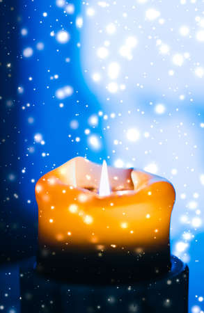 Happy holidays, greeting card and winter season concept - Yellow holiday candle on blue sparkling snowing background, luxury branding design for Christmas, New Years Eve and Valentines Day
