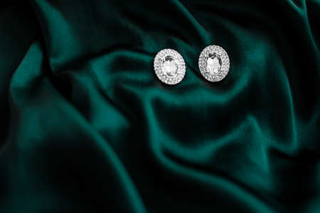 Jewellery brand, elegant fashion and bridal luxe gift concept - Luxury diamond earrings on dark emerald green silk, holiday glamour jewelery present
