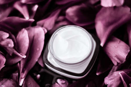 Cosmetic branding, moisturizing and anti-age - Luxury face cream moisturizer for facial skin on pink flower background, floral essense, spa cosmetics and beauty emulsion for skincare brand product Stock Photo
