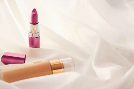 Cosmetic branding, glamour and skincare concept - Beige tonal cream bottle make-up fluid foundation base and pink lipstick on silk background, cosmetics products as luxury beauty brand holiday design Stock Photo