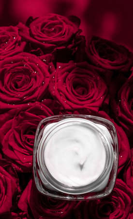Luxe cosmetics, branding and anti-age concept - Face cream skin moisturizer and red roses flowers, luxury skincare cosmetic product on floral background as beauty brand holiday flatlay design