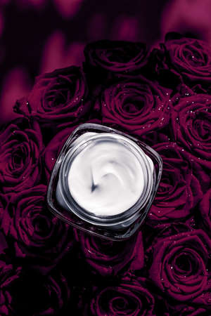 Luxe cosmetics, branding and anti-age concept - Face cream skin moisturizer and dark purple roses, luxury skincare cosmetic product on floral background as beauty brand holiday flatlay design Stock Photo