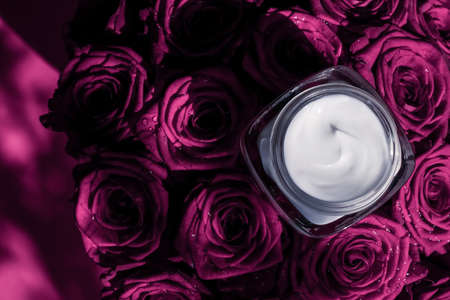 Luxe cosmetics, branding and anti-age concept - Face cream skin moisturizer on pink roses flowers, luxury skincare cosmetic product on floral background as beauty brand holiday flatlay design Stock Photo