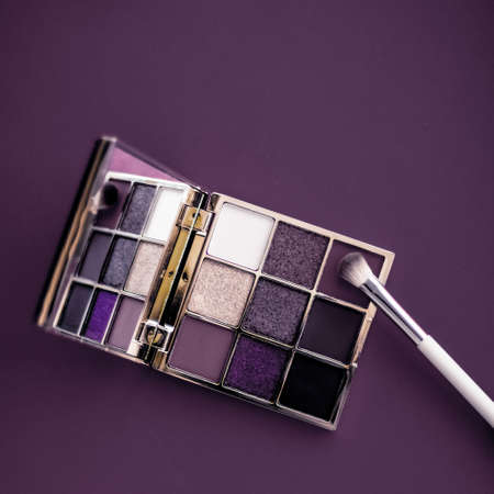 Cosmetic branding, mua and girly concept - Eyeshadow palette and make-up brush on purple background, eye shadows cosmetics product as luxury beauty brand promotion and holiday fashion blog design Фото со стока