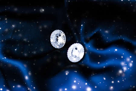Jewellery brand, Christmas shopping and New Years gift concept - Luxury diamond earrings on dark blue silk with snow glitter, holiday winter magic jewelery present