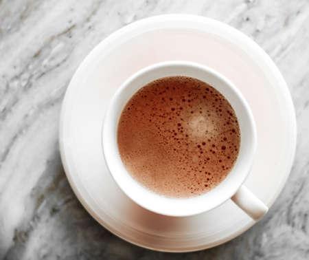 Frühstück, Brunch und Café-Konzept - Morgenkaffeetasse mit Milch auf Marmorsteinplatte, heißes Getränk auf Tischplatte, Lebensmittelfotografie von oben und Rezeptinspiration für Kochblog oder Kochbuch