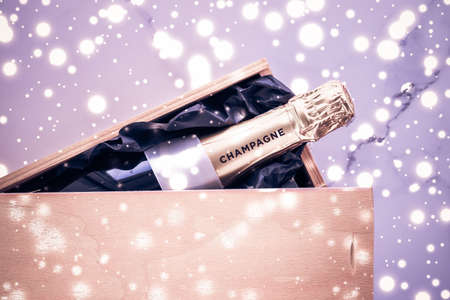 Celebration, drink and branding concept - Champagne bottle and gift box on purple holiday glitter, New Years, Christmas, Valentines Day, winter present and luxury product packaging for beverage brand
