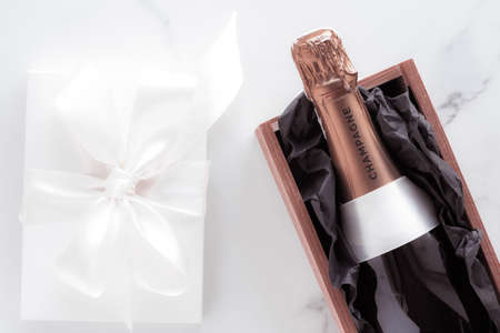 Celebration, drink and branding concept - Champagne bottle and gift box on marble, New Years, Christmas, Valentines Day or wedding holiday present and luxury product packaging for beverage brand