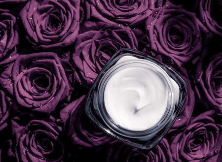 Luxe cosmetics, branding and anti-age concept - Face cream skin moisturizer on purple roses flowers, luxury skincare cosmetic product on floral background as beauty brand holiday flatlay design